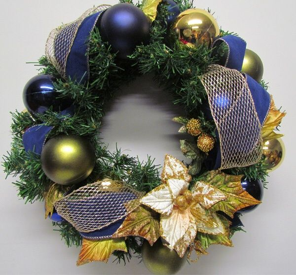 Classic Christmas wreath by Miss Haberdash features cream poinsettia embellished with gold glitter, blue velvet ribbon and gold mesh.