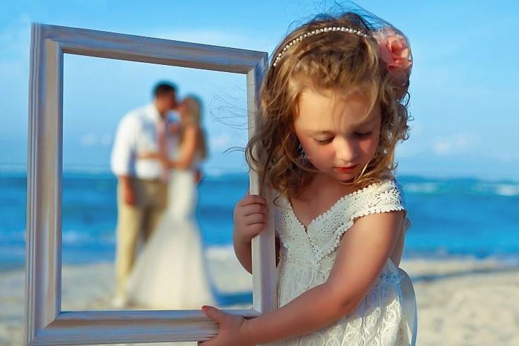 Bride and groom with their daughter (flower girl) holding the frame.. Have to do this!!!