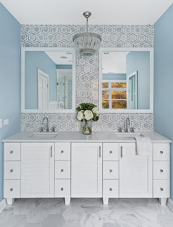 White framed bathroom mirrors are hung from a wall clad in gray marble hex tiles lit by a gray beaded chandelier.