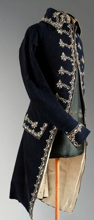 "Frockcoat, late 18th C. France, wool. Navy blue, collar, cuffs and skirts embroidered with cream silk ""point Beauvais"" garlands of pearls and flowers, embroidered buttons.  Coutau-Bégarie"