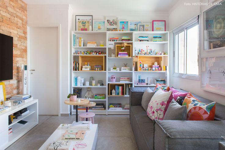 Sala de estar com estante branca com nichos de madeira pinus, sofá cinza e almofadas estampadas.