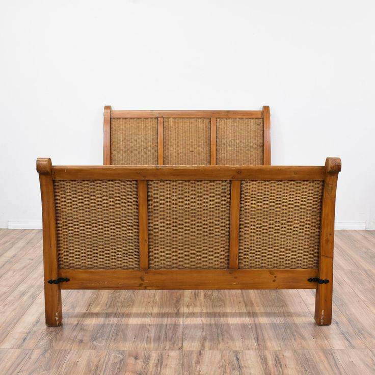 This tropical bed frame is featured in a solid wood with a glossy medium pine finish. This queen sized bed is in great condition with woven wicker panels, a curved headboard and footboard and iron metal details. Beach chic bed perfect for a beachy bungalow! #tropical #beds #bedframe #sandiegovintage #vintagefurniture