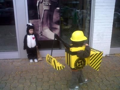 Backhoe loader digger costume!!  We used a diaper box for the body, another box cut in two for a front loader and back loader, lots of black duck tape and hot glue, two cardboard tubes from dry cleaning hangers, yellow spray paint and black Sharpees.