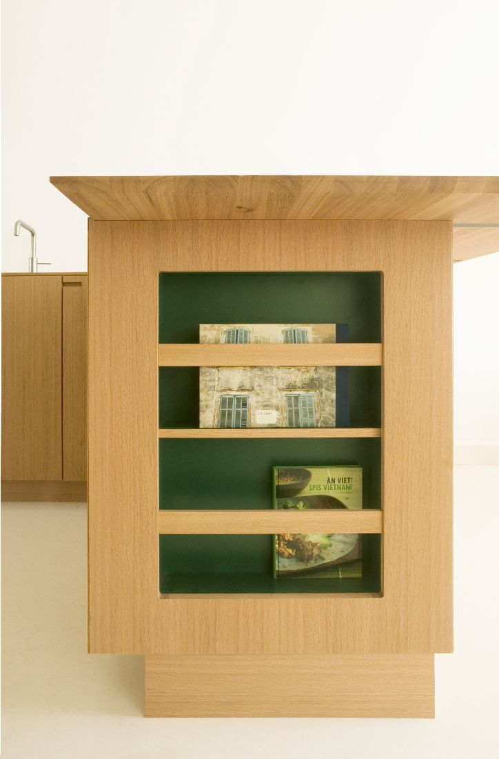 A integrated magazine rack allows for easy storage in this Copenhagen kitchen. #green #laminate #oak #wood #kitchen #scandinavian #magazine #coffebook #interior