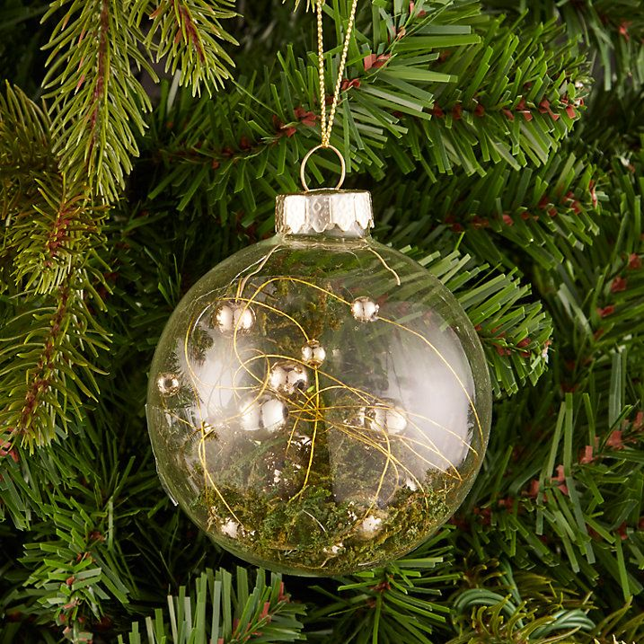 Filled with wonderful extracts of Irish scenery, this glass bauble is an entrancing extension of your Into the Woods tree. Garnished with moss to illustrate the leafy forest as well as speckles of gold and shining pearls to add a little christmas cheer.