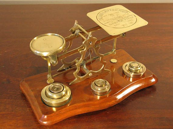Stunning Antique Edwardian Period Postal Letter Scales C1910 A slightly larger than normal, beautiful antique set of postal scales made of polished brass to mahogany wood base on bun feet. With weights, the weight tray is marked Inland Letter Post with weight instructions.  Makes a truly stunning and eye catching piece that has been intricately sculpted in great detail. Is in good condition with minor age related marks. Dimensions: 9 1/2(24.1cm) wide by 5 1/2(13.9cm) deep by 4 3&#x2...
