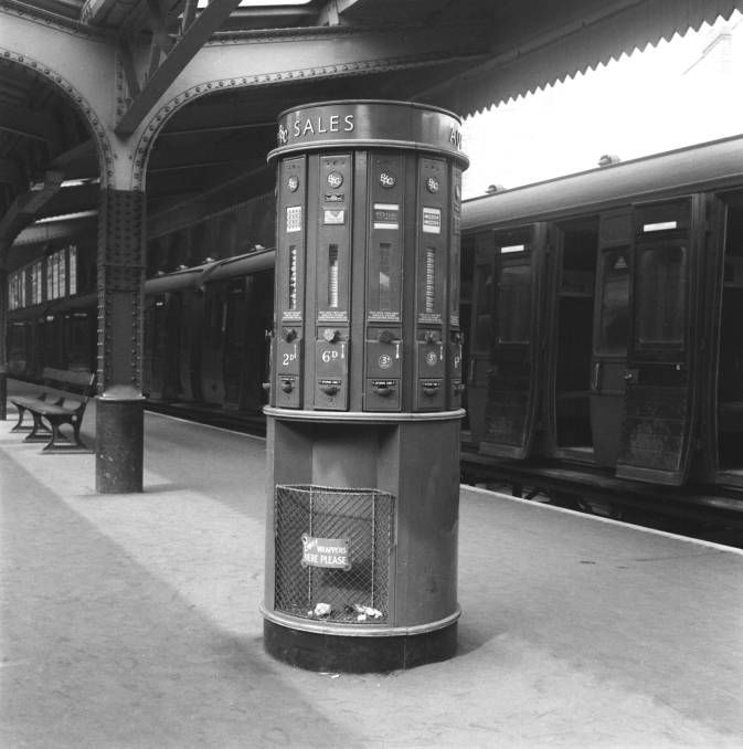 Vending machine in a railway station, 15 March 1956. The machine is selling chocolate and sweets.. These machines were provided by the British Automatic company who also made scales and cigarette and sweet machines.