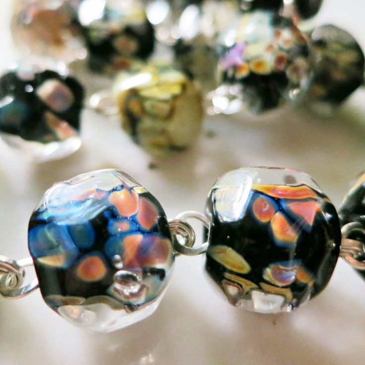 Moon Rocks - a glass bead recipe from Lucinda Storms : Belvedere Beads - make a barrel bead in black glass for the core, then roll in an equal blend of Val Cox 'Raku' and 'Pink Lipstick' frit. Then heavily encase the bead in clear and hand facet.
