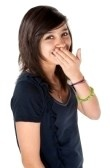 Cute Hispanic teenage girl covering her braces with hands and a big smile stock photography