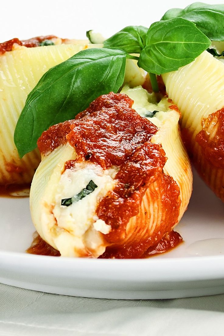 Recipe including course(s): Entrée; and ingredients: asiago cheese, basil leaves, black pepper, cottage cheese, dried oregano, egg, garlic powder, Italian parsley, mozzarella cheese, parmesan cheese, pasta shells, spaghetti sauce