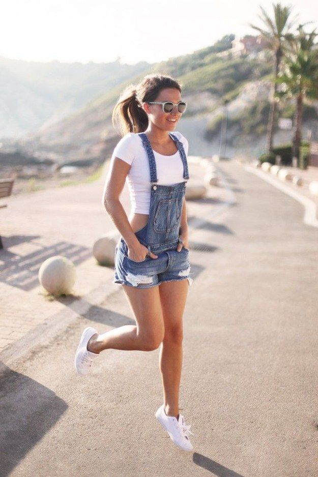 Overol de shorts destruídos con un crop top blanco y un par de tennis casuales para un look deportivo y cómodo. | 18 Looks ideales para las chicas que quieren usar overoles                                                                                                                                                      Más