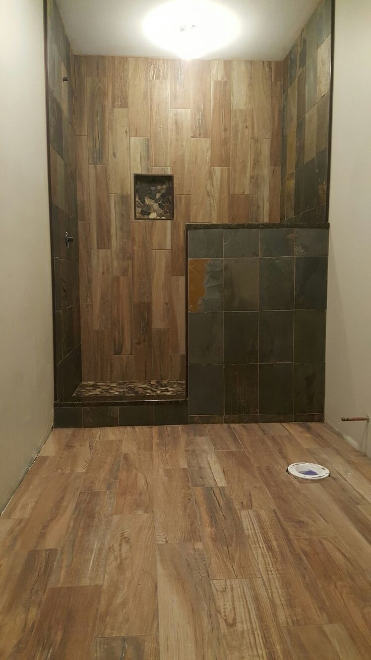Faux wood tile as an accent wall in shower & slate stone on surrounding walk-in shower