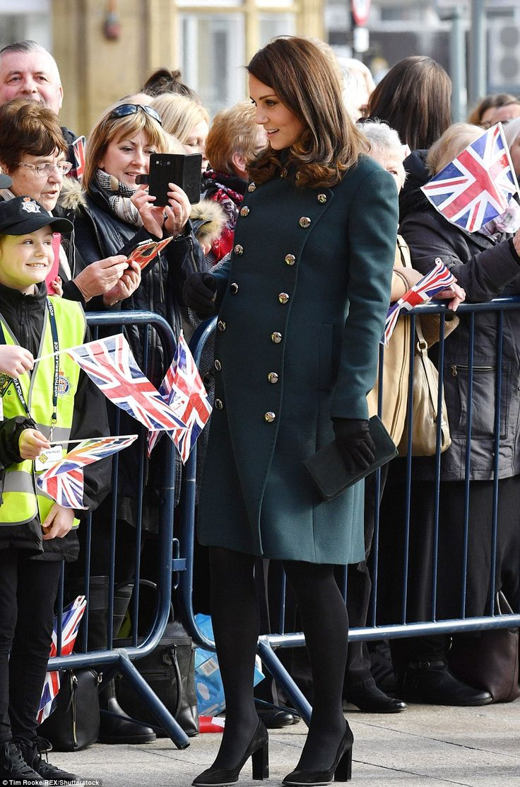 The fitted military style coat showcased the Duchess' ever-growing baby bump, with her thi...