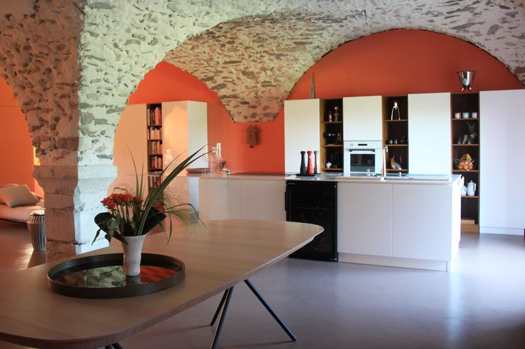 Salle à manger ouverte sur la cuisine blanche et bois avec un plafond voûte en pierre et les murs en tableau orange. Le sol en béton ciré fait ressortir le contraste des couleurs !