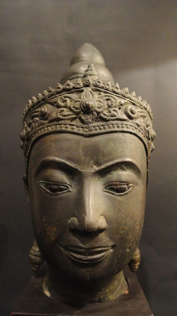 Ayuttaia's buddha head from XVII Century Thailand. Testa di #bhudda thailandese in stile #Ayuttaia, XVII secolo, #Thailandia.  Caratteristiche tipiche delle raffigurazioni di Buddha in questo stile sono l'espressione facciale seriosa e un'ampia varietà di mudra, un altro elemento fortemente caratterizzante è il fiore cruciforme posto sulla corona in cima alla testa della divinità. Ayutthaya fu la capitale della Thailandia dal 1350 al 1767. H: 23, 5 cm. www.arte-orientale.com