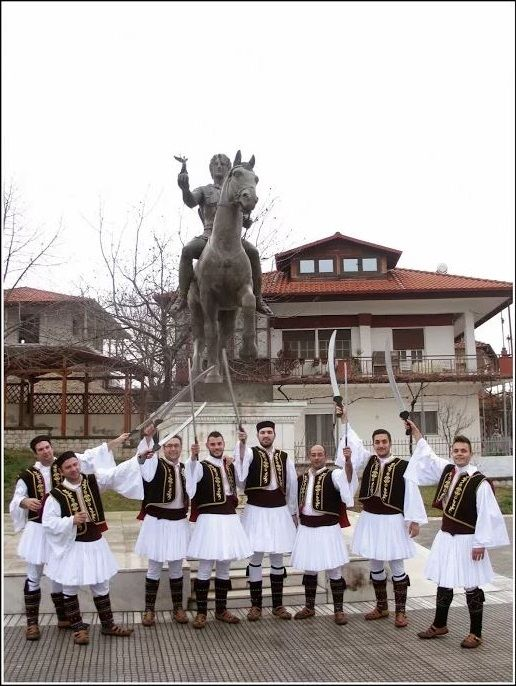 Modern Macedonians in middle ages traditional costume in front of the ancient Macedonian, Alexander the Great statue in Giannitsa, Macedonia, northern Greece.