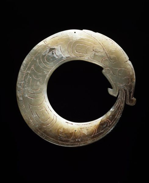 ca. 1100-1000 BCE. Carved Jade Pendant, Coiled Dragon with tail in its mouth. Such items were buried with the owner. Western Zhou Dynasty. China. V&A  (C.T. Loo, no find spot)