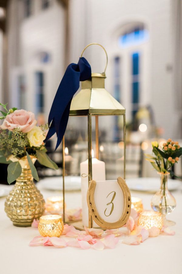 Caged candles and gold DIY horseshoe table numbers: http://www.stylemepretty.com/georgia-weddings/douglasville/2016/09/12/southern-horse-stable-wedding/ Photography: Rustic White - http://www.rusticwhite.com/