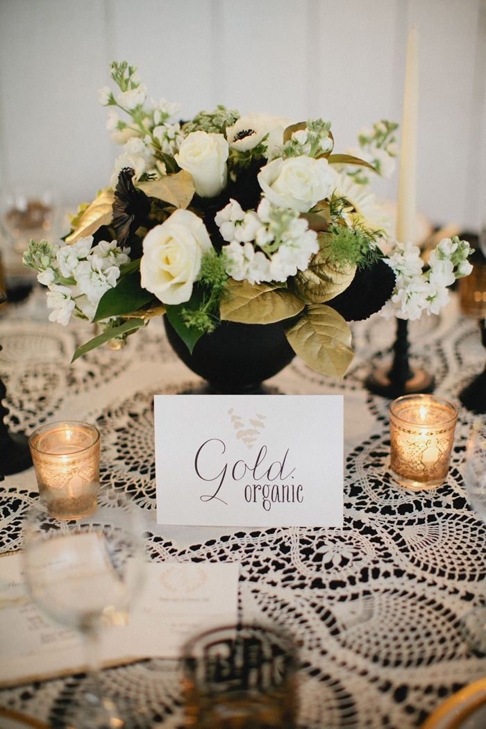 White/Gold Flowers, Black Vase, Candles. Love the Lace Tablecloth.