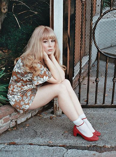 I love everything about this look: Her 60s-French-film-star hair, the neutral floral minidress, the lace-ankle socks, & especially those red ankle-strap shoes. So cute.
