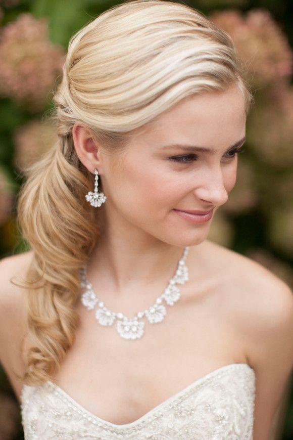 Ein schlichter, lockerer, seitlich getragener Pferdeschwanz - dazu wundervolle Ohrringe und eine dazu passende Halskette! Fertig ist die Braut!