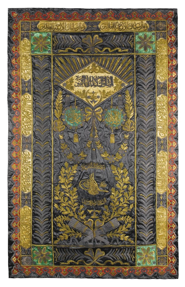 AN OTTOMAN SILK AND METAL-THREAD EMBROIDERED WALL HANGING WITH TUGHRA OF SULTAN MEHMED V (R.1909-18), TURKEY, EARLY 20TH CENTURY the black silk ground embroidered with silver and silver-gilt metal threads with tughra of Mehmed V surrounded by a laurel wreath, with crossed quivers tied with a ribbon and paired garlands above, framed by calligraphic bands and foliate details on red, green and yellow silk grounds 260 by 158cm.