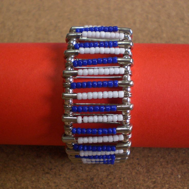 Bracelet made using safety pins with blue and white plastic beads. Connected with silver round beads.