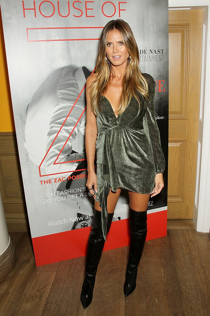Heidi Klum shows off her perfect figure in black knee-high boots and sparkling mini dress.