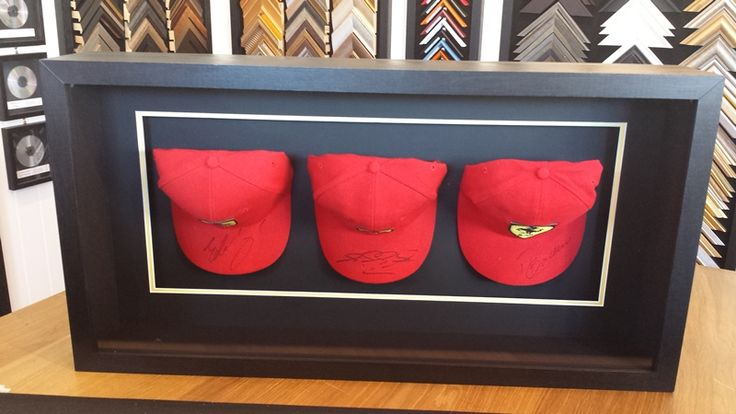 Here's a set of three Scuderia Ferrari caps signed by past F1 drivers Eddie Irvine, Michael Schumacher and Rubens Barrichello, framed in a box frame with low-reflection glass