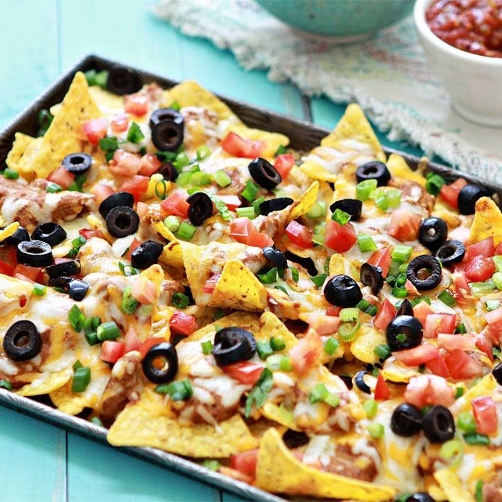 Ultimate Nachos Recipe Appetizers with tortilla chips, refried beans, sour cream, McCormick Chili Powder, McCormick Garlic Powder, Mexican cheese blend, tomatoes, green onions