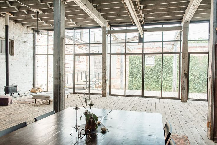 The wall of windows and doors onto Cheryl's courtyard, flooding the warm industrial space with natural light, are a signature architectural element of the home.
