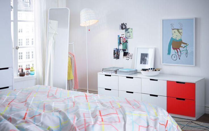 NORDLI modulbyrå med vita och röda fronter, KNAPPER golvspegel, IKEA PS 2014 påslakan, matta, och golvlampa.