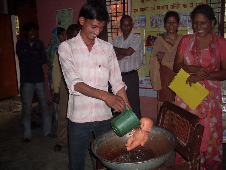 A new father learns to bathe an infant in India as part of a CARE training. CARE found that new fathers desperately wanted to know more about maternal and newborn care, but were too ashamed to ask. So, CARE set up public demonstrations in school yards as part of health fairs - complete with prizes for the most skilled new dads!