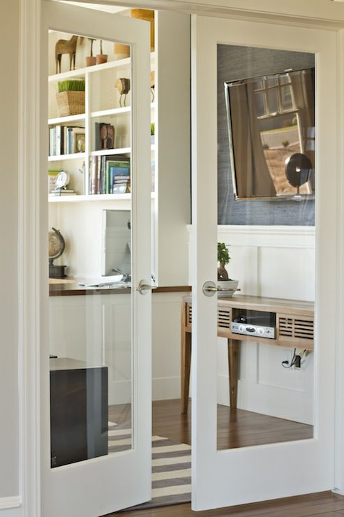 Glass doors to office, modern console table with flat screen, grass cloth walls