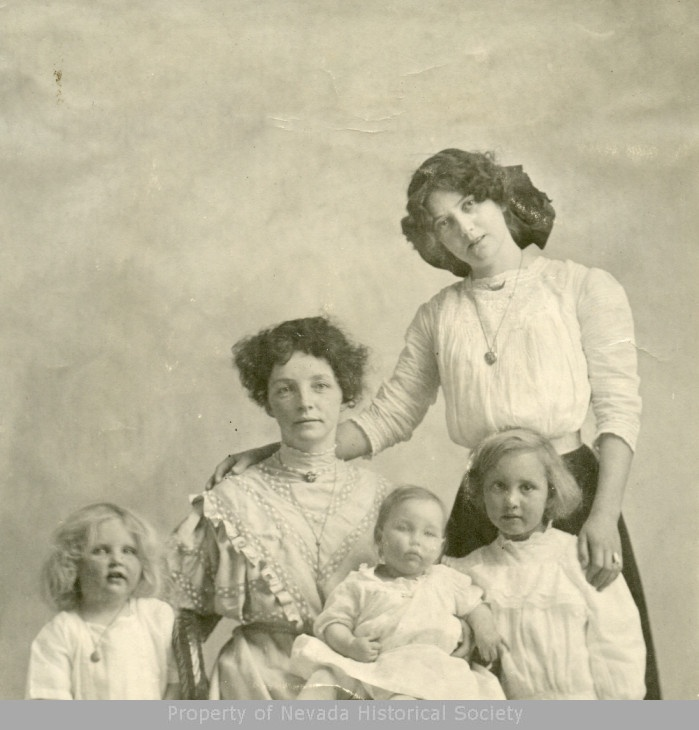 A seated woman with four children around her