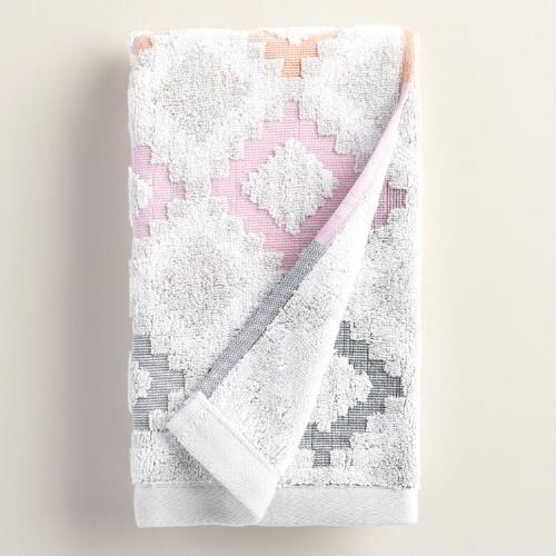 Woven in Portugal of absorbent cotton, our hand towel features a geometric diamond design in a gradation of dark gray to pale coral.