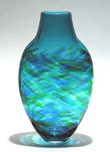 """""""Tall Flattened Vortex Vase: Blue""""  Art Glass Vase    Created by Michael Trimpol  Blown glass with feathery streaks of color that glow in the light. Flattened profile fits neatly on narrow surfaces. Signed on bottom.  Dimensions: 12.0in Hx6.0in Wx3.0in D"""