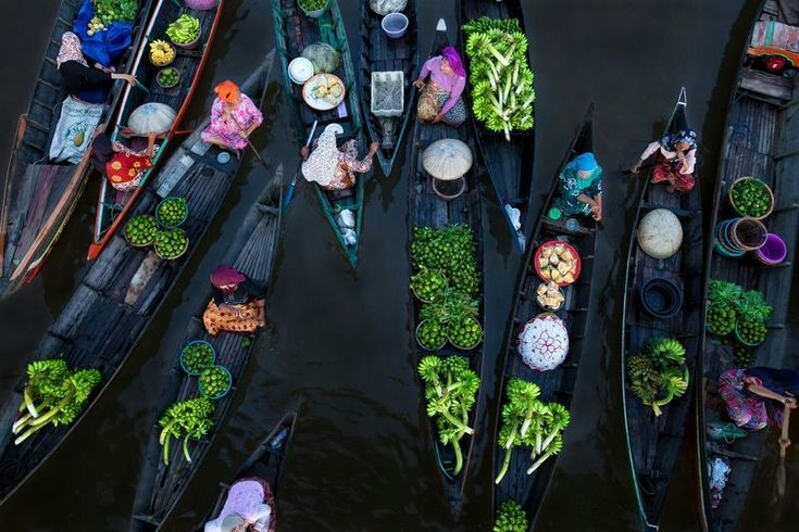 DECEMBER 27, 2017FLOATING MARKET  At the Lok Baintan Floating Market in Indonesia, as many as one hundred boats meet up before sunrise, as they have for 500 years. While the boats float down the river, the women steering them trade products like fresh fruit, vegetables, cakes and meat.  PHOTOGRAPH BY SINA FALKER,
