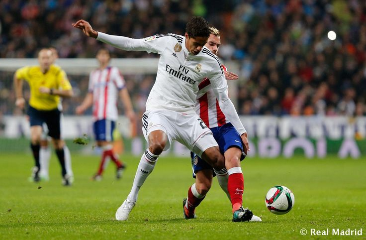 Raphaël Varane of Real Madrid competes for the ball against Antoine Griezmann of Atlético de Madrid during the Copa del Rey round of 16 second leg match between Real Madrid and Atletico de Madrid at Estadio Santiago Bernabeu on January 15, 2015 in Madrid, Spain.
