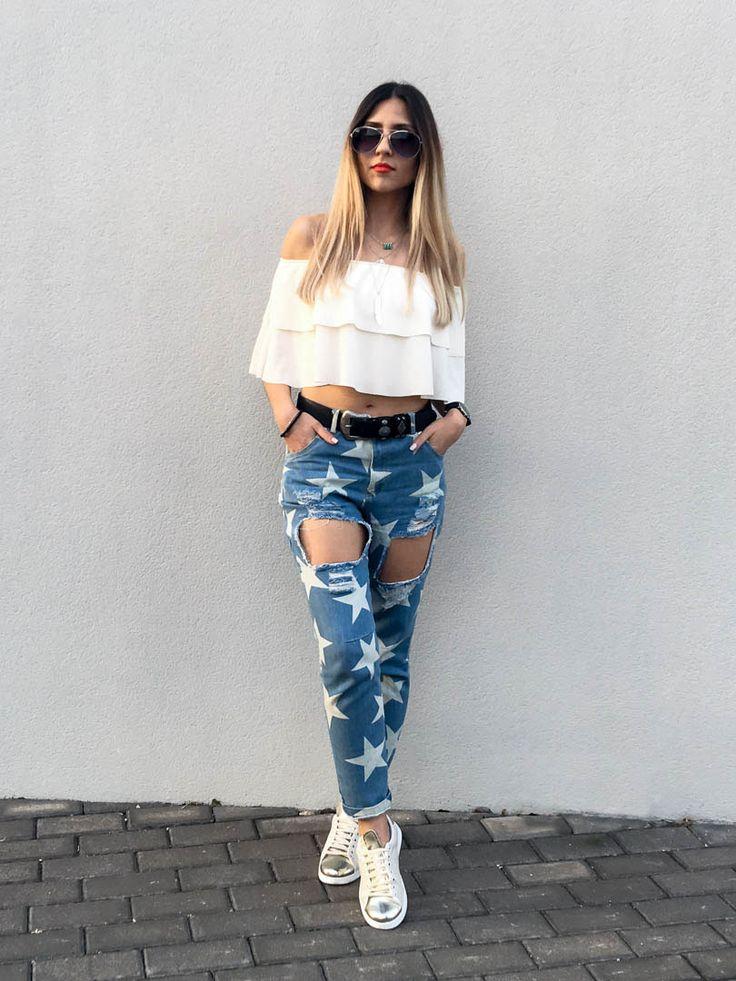 Jeans estilo boyfriend rotos y estampado de estrellas de lupsona, blusa blanca de volantes de hombros descubiertos de tr3x y zapatillas deportivas beige claro y dorado con hilos de colores de calzados victoria.