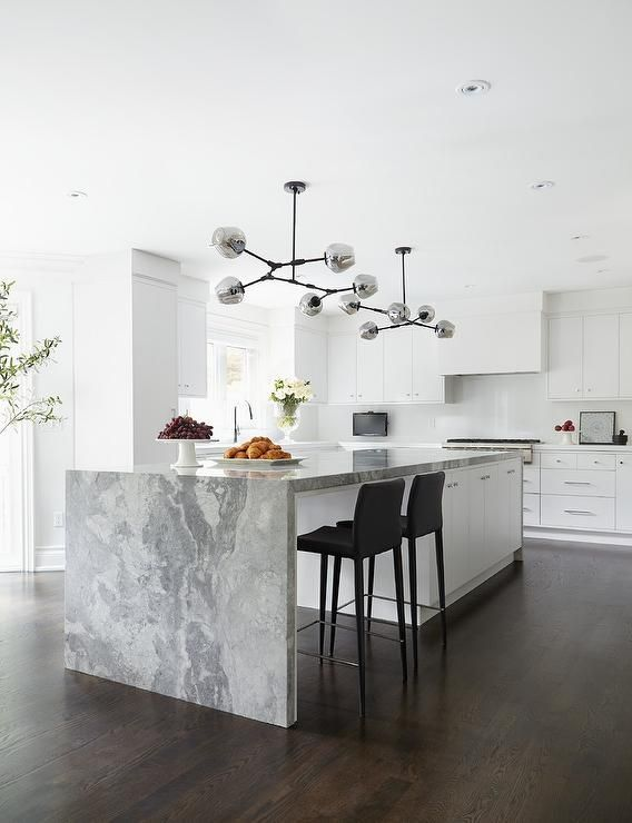 Modern white kitchen is illuminated by gray glass modular pendant lights fixed over a white center island seating sleek black stools at a gray marble waterfall countertop.