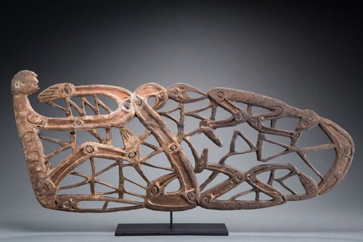 "This beautiful piece is an older Asmat canoe prow decoration. It has a wonderful openwork design depicting numerous figure and animal motifs. A similar example is published in the small book ""Asmat: Art from Southwest New Guinea"" put out by the Tropen Museum in 1961. The prow shows good age, comes from a German collection, dates to the mid 20th century, is 43 1/8"" (109.5 cm) in length"