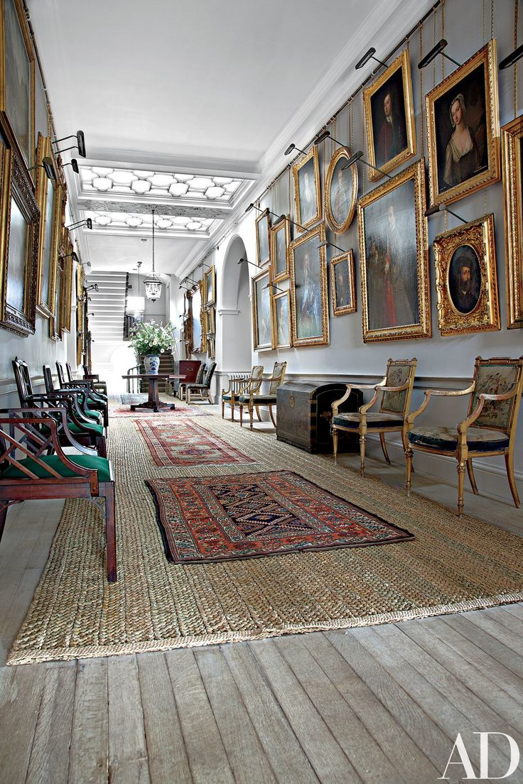 Portraits fill the walls of a skylit gallery, which contains cockpen chairs (possibly by Chippendale) as well as Louis XVI–style gilt-wood armchairs by R. Whytock & Co.; traditional rush matting is scattered with small rugs.