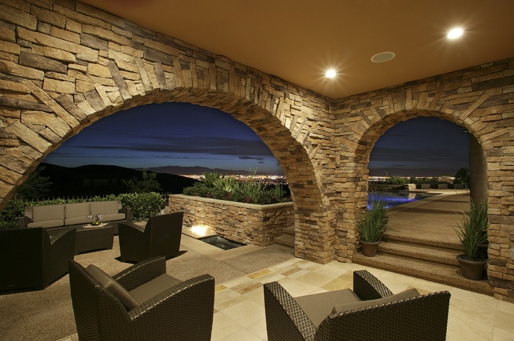 Sheltered outdoor seating area opens to infinity pool deck overlooking Vegas from Christopher Homes