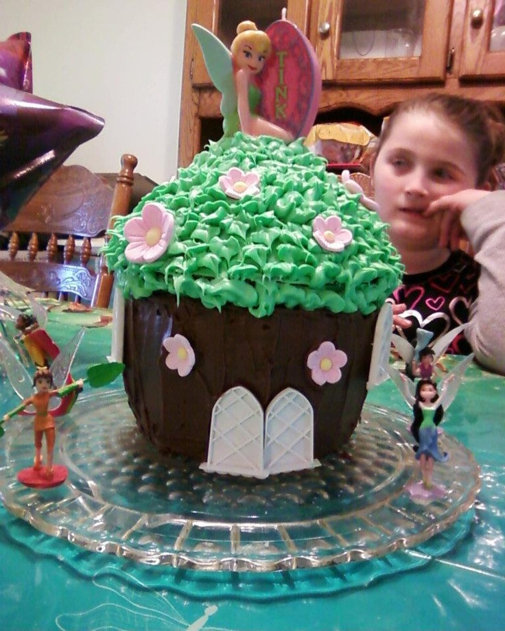 Tinkerbell and friends tree house.  I used a giant cupcake mold to make this. The doors are actually the windows to a castle cake mold set we have. To make Tinkerbell's friend stick we put a little icing under their footing.