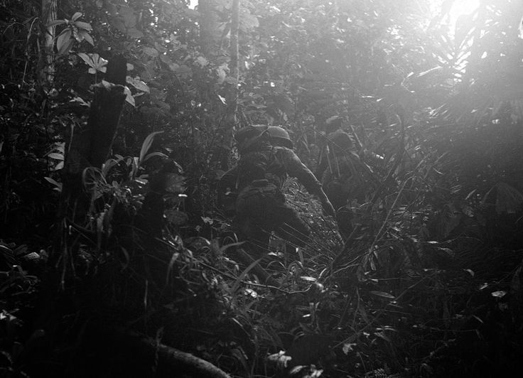 American reconnaissance patrol into the dense jungles of New Guinea, on December 18, 1942. Lt. Philip Winson had lost one of his boots while building a raft and he made a make-shift boot out of part of a ground sheet and straps from a pack.