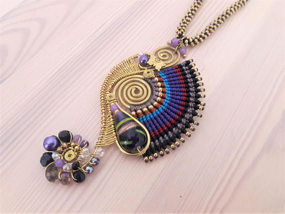 Welcome to Bohemian Style Thai statement necklaces...  You're looking at a stunning, asymmetrical, purple glass bead, wire-wrapped pendant, with macrame waxed cotton in black, red, grey, purple, blue and brown. The bold, purple pendant is decorated with purple and complimentary stones and glass beads, gold brass beads and a butterfly motif. Truly a work of art!      www.bohemianstyleshop.etsy.com