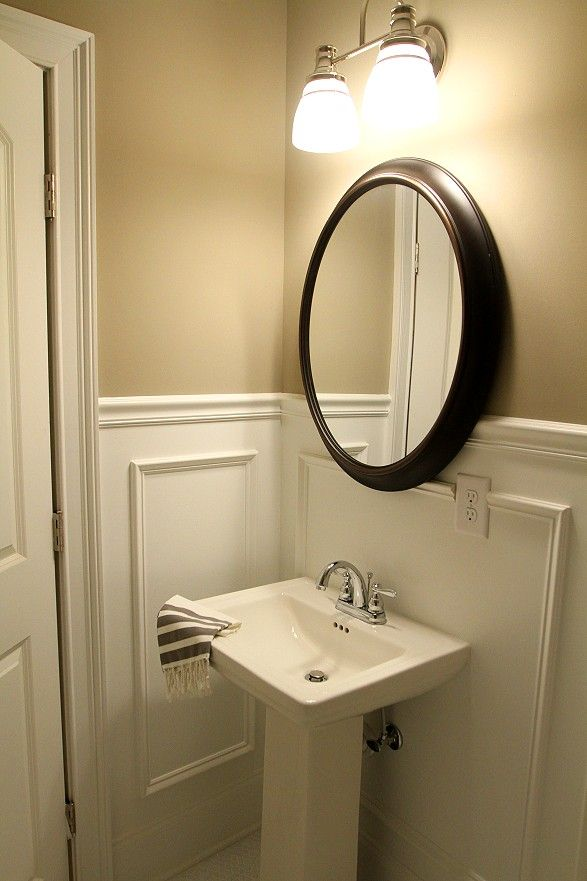 Classy Half Bathroom With Beautiful Molding And Pedestal Sink