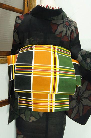 常磐緑、芥子色、黒の三色に赤がアクセントになった大胆な縞に、五筋の縞が交差する格子模様が小粋な単帯です。 #kimono