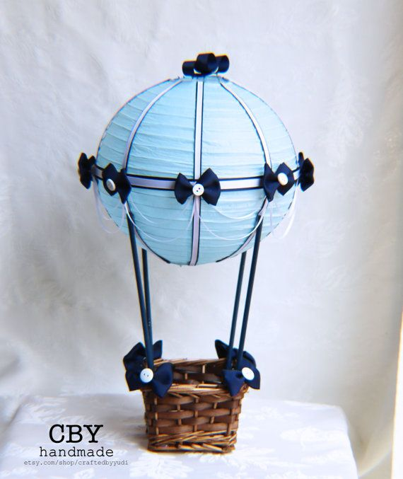 This beautifully handcrafted Hot Air Balloon centerpiece is made using a light blue paper lantern that has been adorned with high quality Navy and White ribbons. It is decorated with white and navy ribbon draping and embellished with navy bows and white buttons. The lantern is attached to a basket that is decorated with navy bows to match.  ** TWO STYLES TO CHOOSE FROM**  Tabletop (shown): The paper lantern is held up using 4 wooden dowels, painted to match that are attached to the basket…